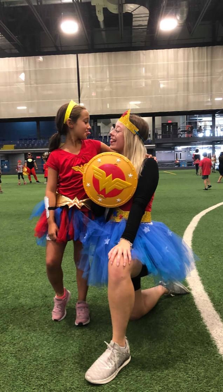 Enfant et animatrice de camp de jour déguisées en WonderWoman